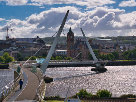The Peace Bridge across the River Foyle in Derry - Londonderry in Northern Ireland, UK. The bridge links the