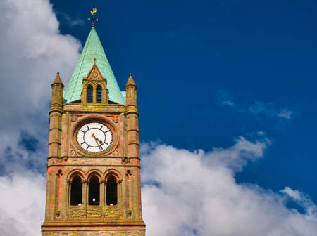 The clock tower of the Guildhall in Derry ~ Londonderry. Taken on a sunny day with blue sky and white clouds. Editorial