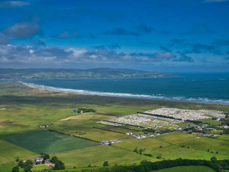 The sweeping arc of Benone Beach in Ulster / Northern Ireland on a sunny day in summer. Green agricultural land and caravan holiday parks appear in the foreground with County Donegal in the distance.