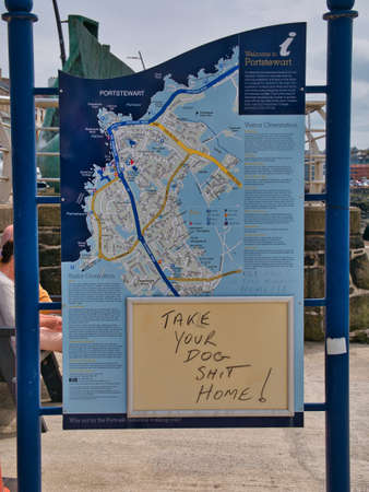 A hand written message on a tourist information sign asks dog owners to clean up after their dog.