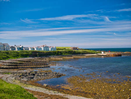Breakwater groynes extending into the sea at low tide at the bay at Portballintrae on the Antrim Causeway Coast in Northern Ireland, UK. Taken on a sunny summer day. Editorial
