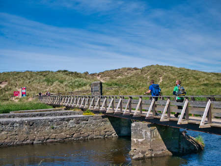 Two walkers cross the Three Quarter Mile wooden footbridge over the River Bush near Runkerry Beach on the Anrtim Causeway Coast in Northern Ireland, UK.