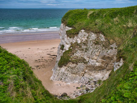 Coastal cliffs showing exposed strata near Portrush on the Antrim Causeway Coast Path - these rocks are of the Hibernian Greensands Formation and Ulster White Limestone Formation - chalk and sandstone