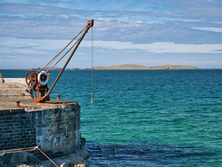 An abandoned, rusting steel crane and winch at the side of a pier in Portrush, Northern Ireland, UK - taken on a sunny day in summer with blue sky and turquoise water. Standard-Bild