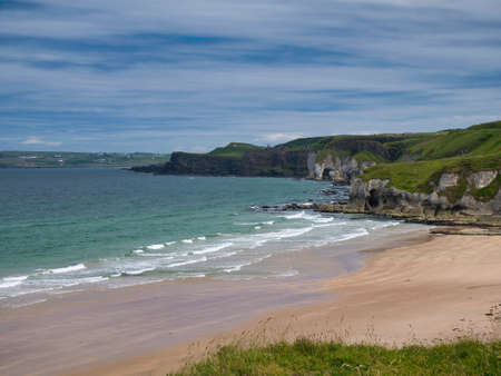 The pristine sand of Whiterocks Beach and coastal cliffs on the Antrim Causeway Coast in Northern Ireland, UK. Taken on a sunny day in summer with light clouds and a blue sky.