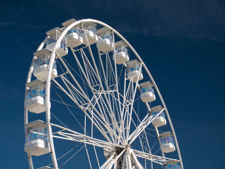 On a sunny day in summer against a deep blue sky, the white steelwork and gondolas of the big wheel tourist attraction at Portrush on the Antrim Coast in Northern Ireland, UK