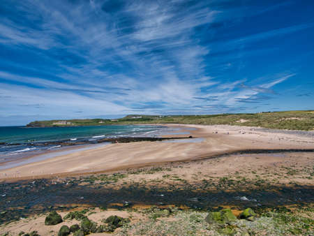 The pristine sands of Runkerry Beach near Port Ballintrae on the Northern Ireland Antrim Causeway Coast, taken on a sunny day in summer with a blue sky and high cirrus clouds Standard-Bild