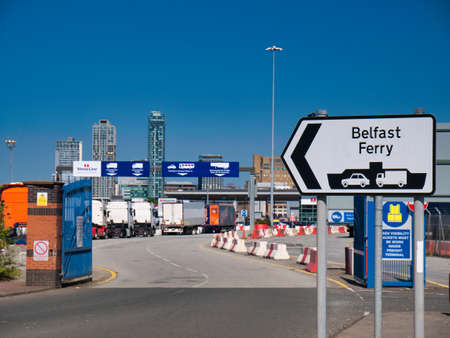With foreground focus set on the Belfast Ferry sign, lorries queue the Stena Line roll on - roll off Liverpool to Belfast ferry Terminal in Birkenhead on the River Mersey.