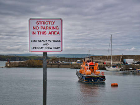 At Portrush Harbour in Northern Ireland, a sign with red text on a white background states that no parking is allowed, except for emergency vehicles and lifeboat crew. Editorial
