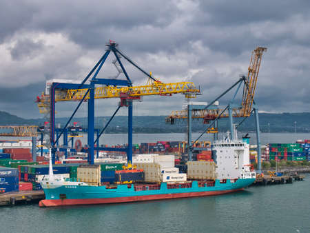 Container ship Ragna loading and unloading at the Belfast Harbour container terminal on an overcast Sunday morning in July 2021