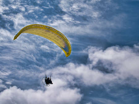 A pilot flies a yellow paramotor above Benone Strand (Beach) on the Atlantic Coast of Northern Ireland. Taken on a sunny day with white clouds.