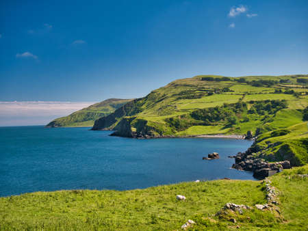 From Torr Head, clear blue water and green hills around the spectacular Antrim Causeway Coast in Northern Ireland, UK - taken on a calm, sunny day in summer with blue sky and blue water.