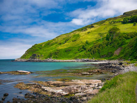 The clear blue water and green hills around Murlough Bay on the spectacular Antrim Causeway Coast in Northern Ireland, UK - taken on a calm, sunny day in summer with blue sky and blue water.