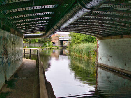 The darkened towpath of the Leeds Liverpool Canal as it passes under a rivetted metal bridge and pipework at the A5057. A grafitti covered wall appears on the left.