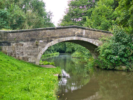 An old stone bridge reflected in the water of the Leeds Liverpool Canal in a rural setting on the  in Lancashire, UK.