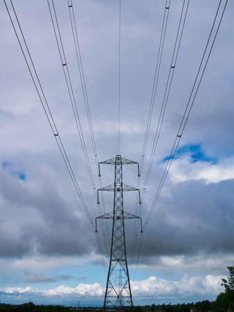 A high voltage electricity transmission pylon and overhead power lines - part of the national grid for the distribution of power by overhead cables in the UK. Taken on a day with clouds and blue sky.