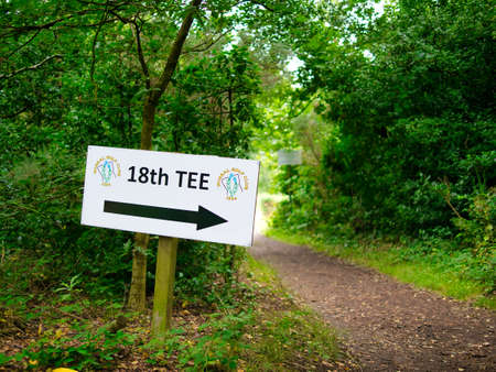 A white sign board in a woodland area at a golf club points a large black arrow in the direction of the 18th Tee, the last hole on the golf course.