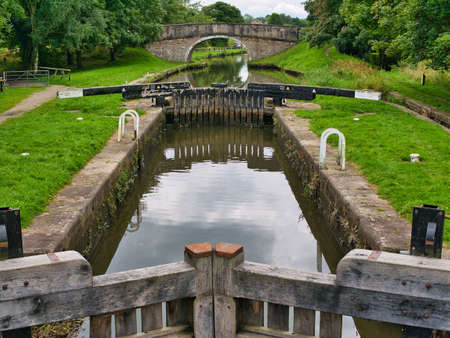 Runnel Brow Lock (No 3) and in the background Runnel Brow Bridge on the Rufford Branch of the Leeds Liverpool Canal. Taken on an overcast day in summer with reflections in the calm water.