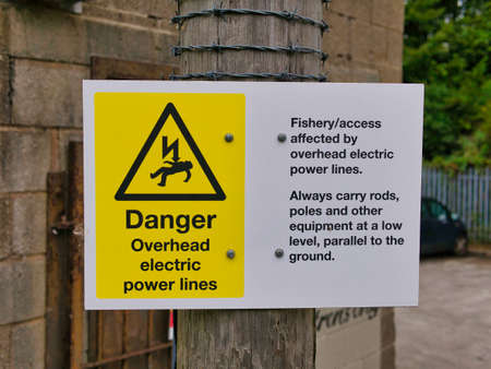 A yellow and white danger sign on the Leeds to Liverpool Canal in Lancashire, UK warning anglers of overhead electric power lines and the risk of electrocution.
