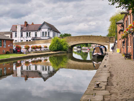 Burscough wharf and the bridge carrying road traffic on the A59 across the Leeds to Liverpool Canal in Burscough, Lancashire, UK - taken on a calm day in summer.
