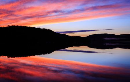 Beautiful and colorful symmetrical sunset over a lake Stock fotó