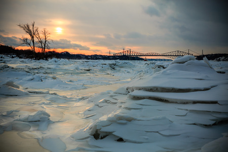 laurent: Cold sunset over the St. Laurent river. You can see the Qu?bec City bridges in the background. Stock Photo
