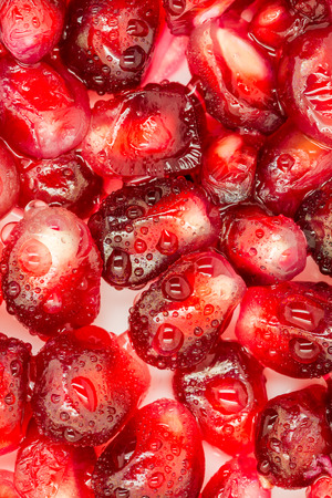 Macro shot of pomegranate seeds covered with droplets