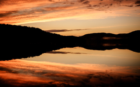Great autumnal sunset over a calm lake