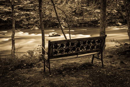 flowing river: Park bench near a rapid flowing river