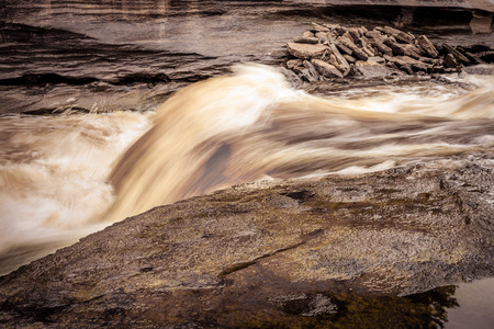 Rainy day near a turbulent flowing river
