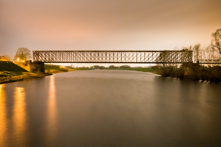 Old industrial railway railroad iron bridge center perspective over river in night
