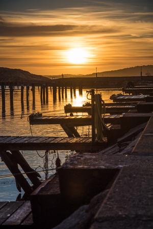 Orange and yellow sky above harbor sunset dock Stock Photo