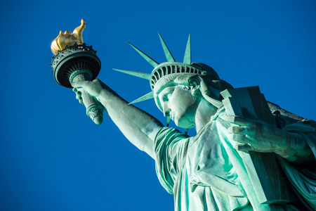 Portrait Statue of Liberty at perfect weather conditions blue sky copper torch Stockfoto