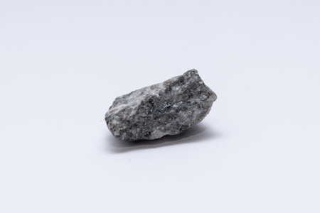 Granite rock stone little bolder in front of white background
