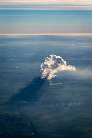 Smoke and steam of a power plant with shadow on the ground in Germany