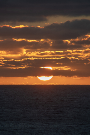 Sun nearly touching the horizon partly covered by red shining clouds at Indian Ocean