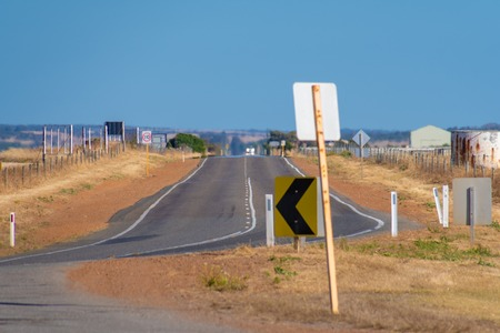Endless straight road through dry farmland in the Australian Outback