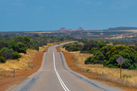 Road leading over small hills in australian bush landscape during hot spring