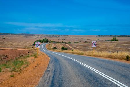 Australian bush road leading through dry landscape and farmland with speed limit 110 kph