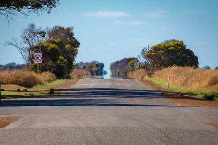 Endless straight road in Australian Outback with hot sun causing Fata Morgana