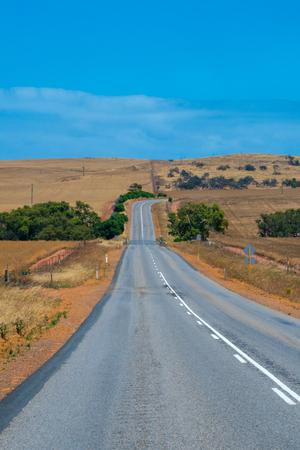 Australian bush road leading through dry landscape and farmland with empty road
