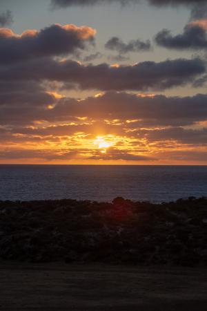 Sun shining through orange clouds during sunset at the coast of Geraldton, Western Australia