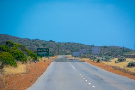 Road towards pink lake in Australian summer with shimmering air due to hot sun Stockfoto