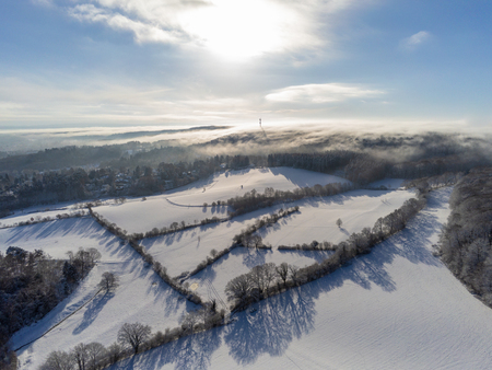 Snow covered landscape during sunny winter day in the Eifel region aerial shot