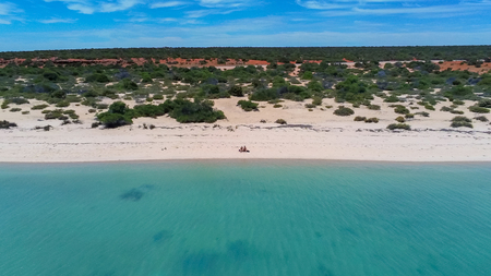 Young couple sitting at lonely beach in Shark Bay in Western Australia Stockfoto