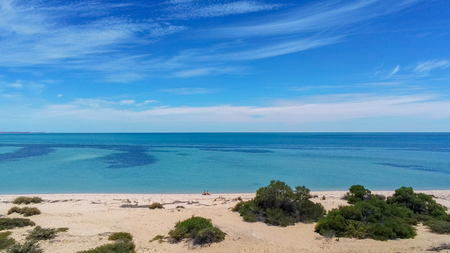 Young couple sitting at empty beach in Shark Bay in Western Australia