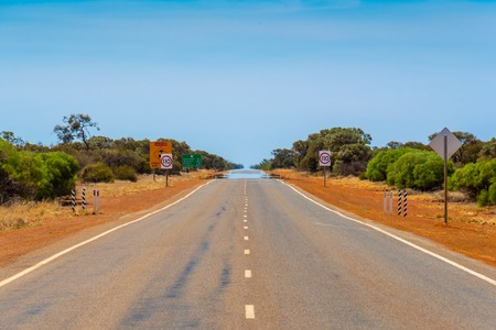 Mirage on an endless straight road in Western Australia close to Billabong Roadhouse