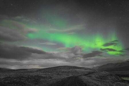 Aurora in Iceland northern lights bright beams rising green over hiking path and clouds in black white and accent color 版權商用圖片