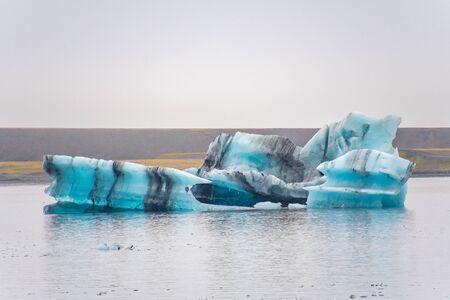 Joekulsarlon Glacier Lagoon deep blue iceberg with dark layers of volcanic ash forming regular pattern
