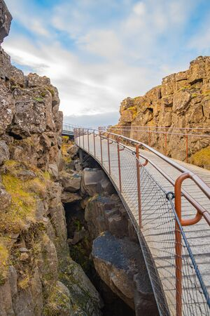 Thingvellir National Park in Iceland during sunny weather hiking path bridging over the canyon